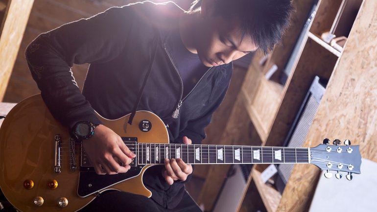 Um garoto jovem tocando uma guitarra Les Paulo